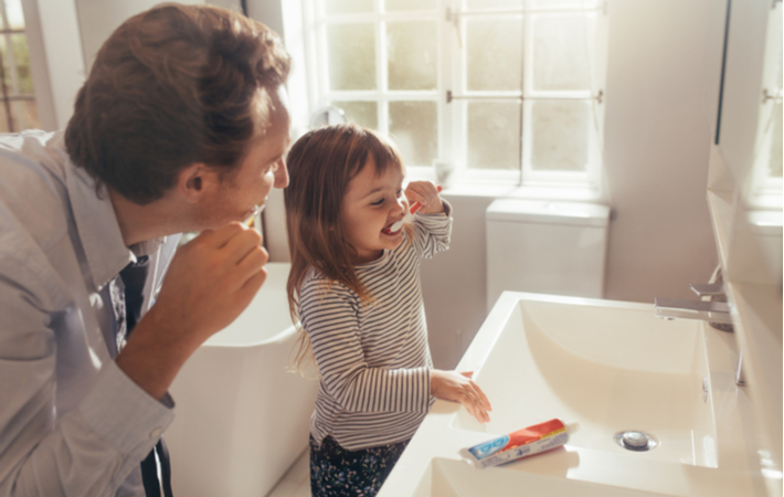 father and daughter brushing teeth together in bathroom